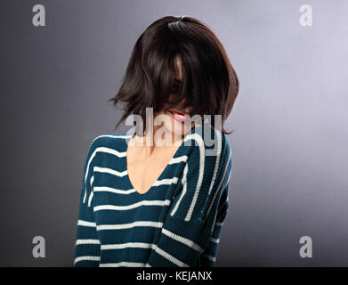 Beautiful smiling enjoing woman moving and shaking her short black hair style with red lipstick on grey background - Stock Photo