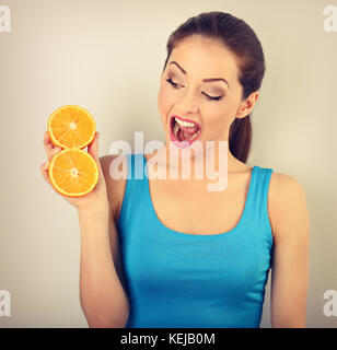 Beautiful excited fun young healthy woman with opened mouth holding slices of oranges in the hand and looking on - Stock Photo