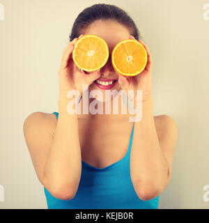Beautiful toothy smiling fit young healthy casual woman holding slices of oranges in the hands near the eyes . closeup - Stock Photo