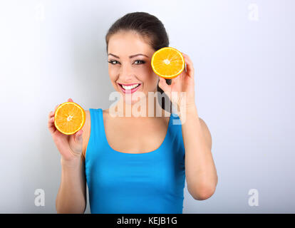 Beautiful toothy smiling fit young healthy casual woman holding slices of oranges in the hands. closeup portrait - Stock Photo