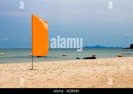 The orange flag on beach, sea background - Stock Photo