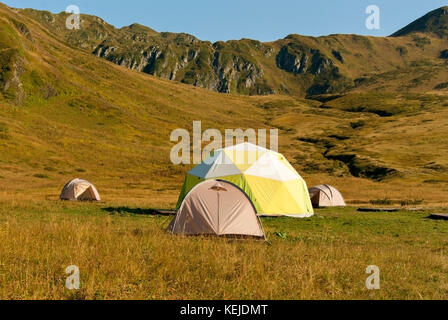 one patient and three small dome tents in the mountain valley - Stock Photo