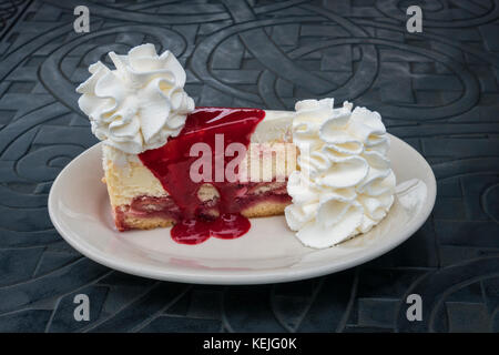 A slice of Raspberry and Cream Cheesecake from The Cheesecake Factory in Baltimore, Maryland, USA - Stock Photo