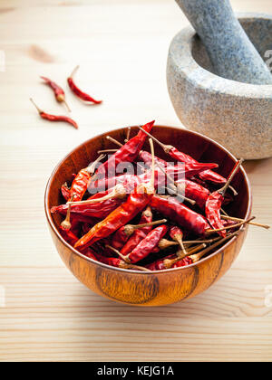 Dried Chillies on white wooden background with mortar and pestle. Selective focus depth of field. - Stock Photo