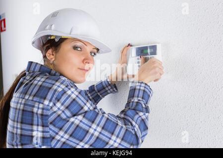 technician installing security system door sensor - Stock Photo