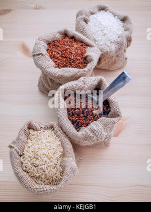 Mixed whole grain traditional thai rices best rices for healthy and super food in hemp sacks bag setup on wooden - Stock Photo