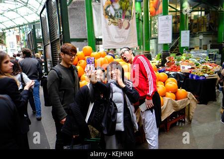 Chinese tourists taking selfie, Borough Market, SE1, London, United Kingdom - Stock Photo