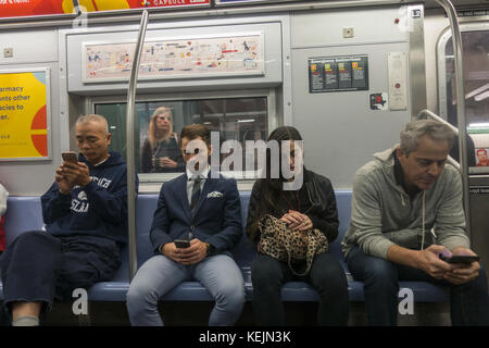 With wifi in all NYC subway stations now people are constantly on their cell phones, talking, texting, using internet - Stock Photo