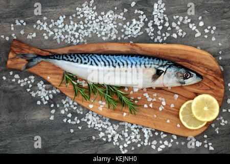 Mackerel fish health food on an olive wood board with course salt, rosemary herb and lemon fruit on marble background. High in omega 3 .