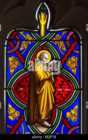 St Matthew - part of stained glass window in church of St Peter's at Stourton, Wiltshire in October - Stock Photo