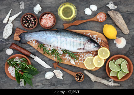 Rainbow trout health food on an olive wood board with seasoning. Very high in omega 3 fatty acid and beneficial - Stock Photo