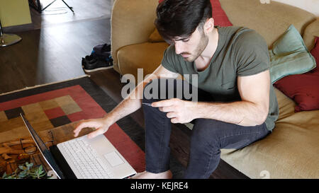 Serious handsome young man sitting on couch at home using credit card to buy things online with his laptop computer - Stock Photo