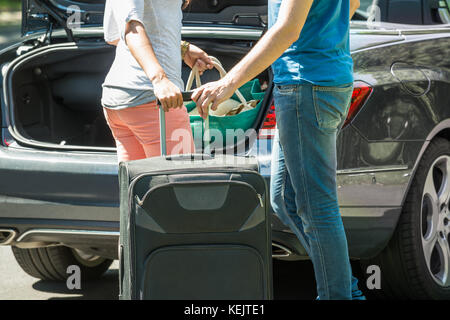 Close-up Of Couple Putting Luggage In A Car Trunk - Stock Photo