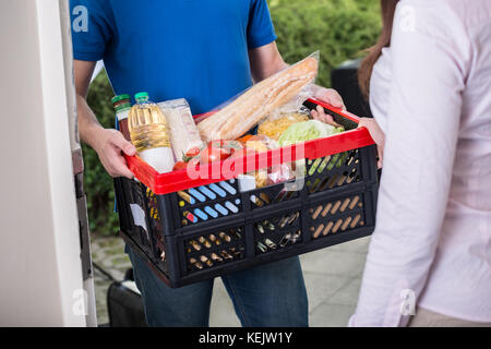 Close-up Of Man Delivers Crate Of Groceries At Home - Stock Photo