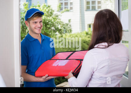 Friendly Delivery Man Handing Pizza To A Customer - Stock Photo