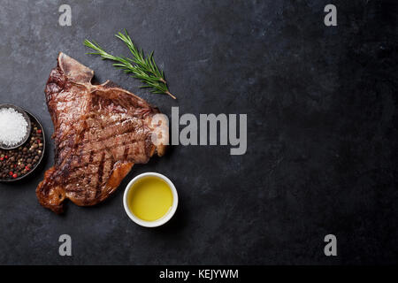 Grilled T-bone steak on stone table. Top view with copy space - Stock Photo