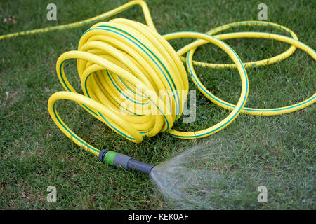 Yellow plastic hose pipe in the garden - Stock Photo