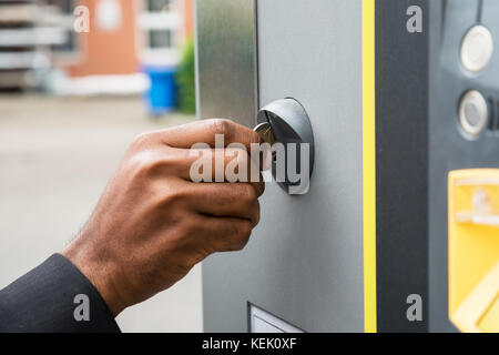 Close-up Of Person's Hand Inserting Coin Into Parking Meter - Stock Photo