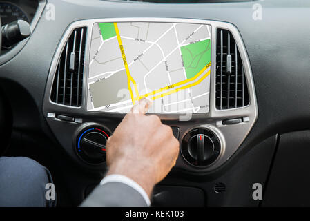Close-up Of Person's Hand Using GPS Navigation System In Car - Stock Photo