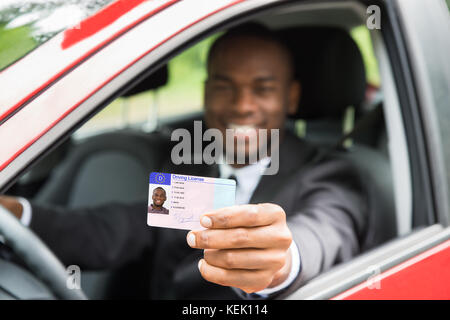 Happy Young African Businessman Showing His Driving License From Open Car Window - Stock Photo