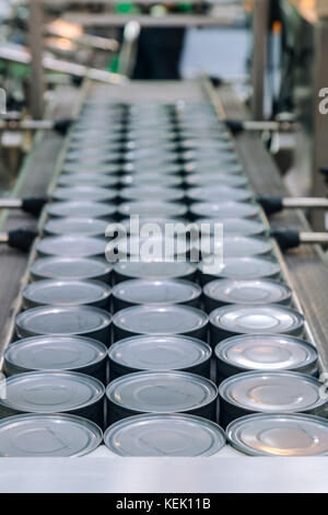 aluminum cans for food processed in factory line conveyor machine at canned food manufacturing, selective focus. - Stock Photo