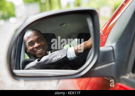 Reflection Of Happy Young Businessman In Rear View Mirror Of Car - Stock Photo