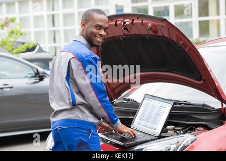 Young Happy Mechanic Using Laptop In Front Of Open Car Engine - Stock Photo