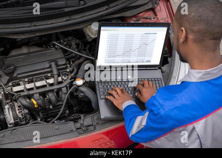Young Male Mechanic Using Laptop While Examining Car Engine - Stock Photo