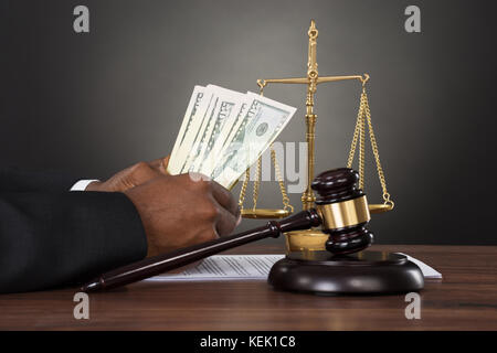Close-up Of A Judge Hands Counting Dollar Banknotes In Front Of Gavel And Scales - Stock Photo