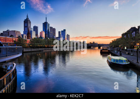 Melbourne city CBD on waterfront along Yarra river with Flinders station and Prince bridge at sunrise reflecting - Stock Photo