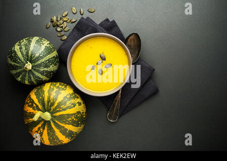 Pumpkin and vegetable soup with cream on dark background Top view - Stock Photo