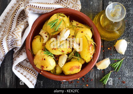 Oven cooked potato with rosemary, garlic, olive oil and mix of spices in a traditional ceramic bowl. Mediterranean - Stock Photo