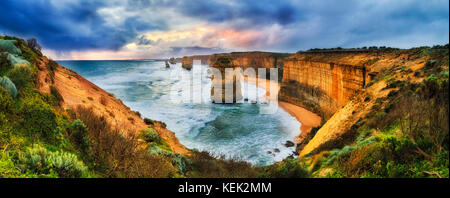 Stormy colourful sunset over twelve apostles marine park on Great Ocean road from lookout towards limestone standing - Stock Photo
