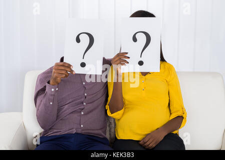 Young African Couple Sitting On Sofa Holding Question Mark Sign In Front Of Face - Stock Photo