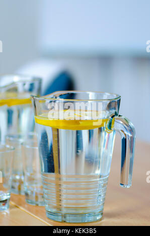 Close-up photo of a glass jug with water and slices of lemon on a wooden table in the office before a meeting - Stock Photo