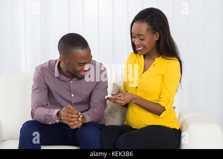Young Expectant Couple Sitting On Sofa Looking At Pregnancy Test - Stock Photo