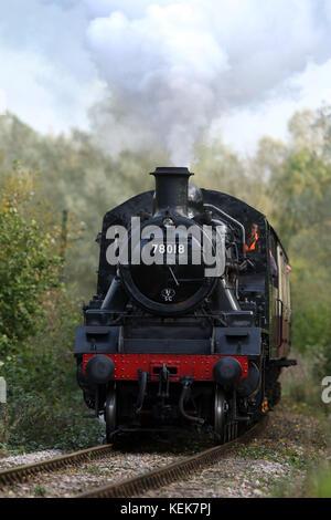 Peterborough, UK. 21st Oct, 2017. A steam locomotive train 78018 powers its way through Nene Park in Peterborough - Stock Photo