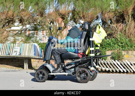 Disabled senior man riding on a mobility scooter in the UK. - Stock Photo