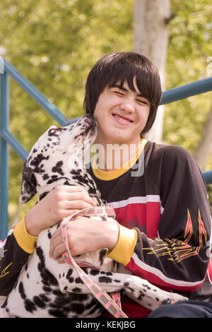 Child hugging dog Young person teen holding and playing with dog showing affection to owner dog kiss kisses licking - Stock Photo