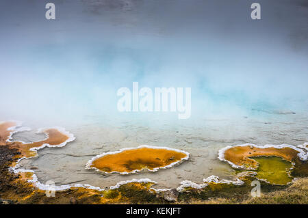 Colorful bacterial mats and mineral deposits line many of the springs located in Yellowstone National Park creating - Stock Photo