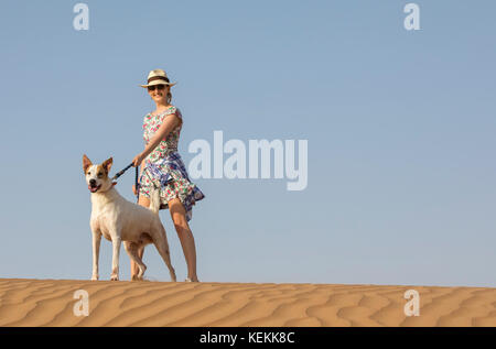 young woman with a stray dog in a desert - Stock Photo