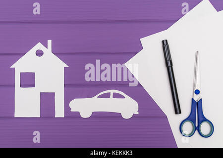 The silhouettes cut out of paper of car and house, scissors and marker near on a white sheet of paper on purple - Stock Photo