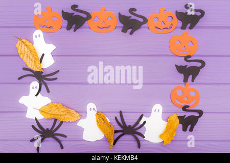 Halloween round frame with different paper silhouettes of pumpkins, cats, ghosts and spiders with autumn leaves - Stock Photo