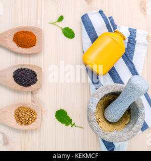 Dried mustard seeds black and yellow  with turmeric powder in wooden spoons and mustard poder in the mortar on rustic - Stock Photo