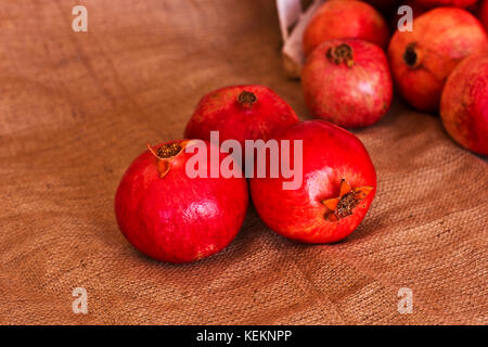 Ripe red pomegranates on the brown burlap - Stock Photo