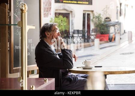 Lyon, 1. Arrondissement, Rue des Capucins, ein Mann sitzt in einem Cafe - Stock Photo