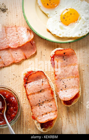Bread slices with tomato relish, turkey rasher and fried egg - Stock Photo