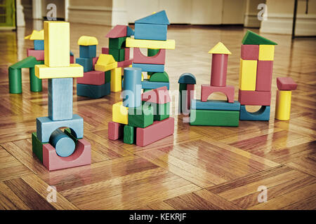 Colorful wooden building blocks on hardwood floor. - Stock Photo