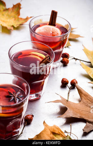Hot red tea with lemon on light gray table with copy space, delicious autumn mulled wine drink