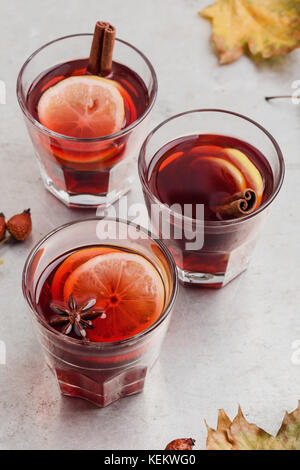 Hot red tea with lemon on light gray table with copy space, delicious autumn mulled wine drink - Stock Photo